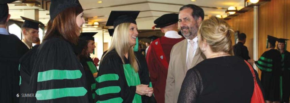 Elizabeth Cockerill (OD/MS'09), Lindsay Hoffbuhr (OD'09), Jeff Myers (OD'84), and Joyce Myers (back to camera) at Convocation