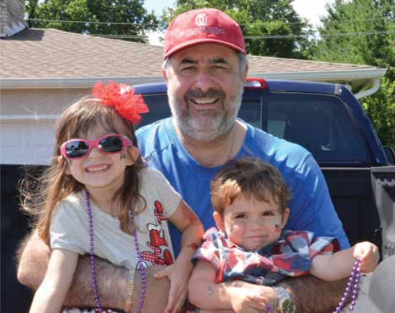 A lapful of grandchildren celebrating the Fourth of July. From left, granddaughter Isla, Jeffrey Myers (OD'84), and grandson Sladen.